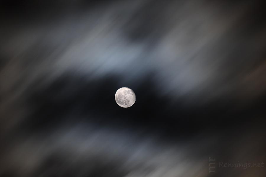 Wolken ziehen im Sturm vor dem Mond vorbei.